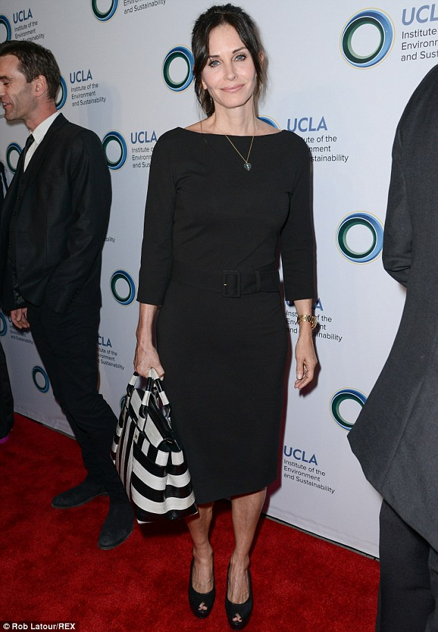 Simple elegance: Couteney wore a belted black dress, peep-toe wedges and a black-and-white handbag