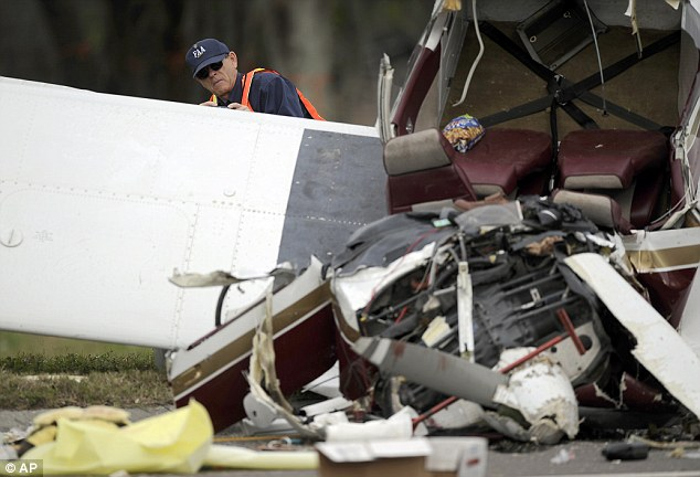 Crumpled: An investigator from the FAA takes photographs of the small single-engine plane