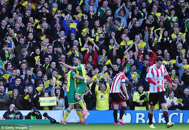 It was all yellow: Robert Snodgrass celebrates in front of home fans after his goal puts Norwich in the lead