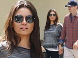 Trying to hide something? Mila Kunis stepped out, holding hands with her 36-year-old beau, sporting yet another loose fitted top that cloaked the shape of her stomach