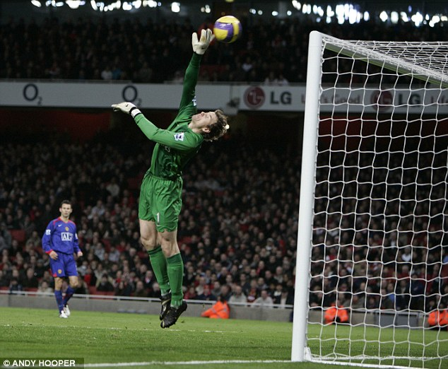 Full stretch: Jens Lehmann tips a volley from Wayne Rooney over the crossbar