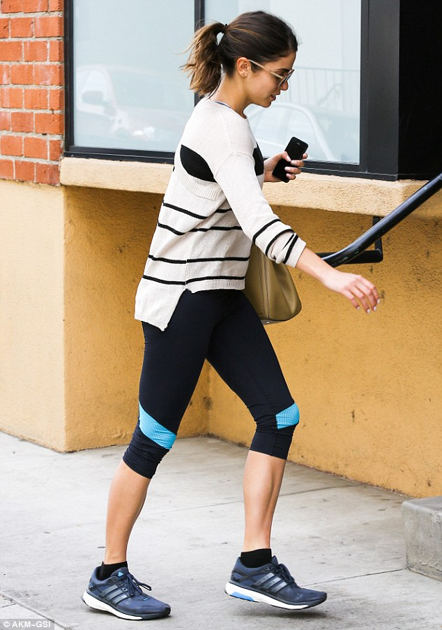 Let's get physical: Nikki wore a loose fitting striped sweater, leggings and well-worn Adidas trainers for her latest gym visit