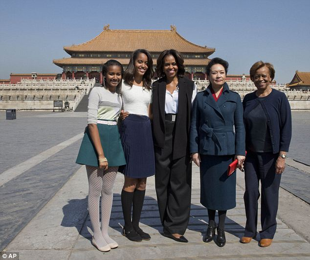 Say cheese! Sasha, Malia, Mrs Obama, Peng Liyuan, and Marian Robinson pose for a photo in front of the Forbidden City on Friday