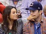Under the thumb! Mila Kunis playfully silences fianc� Ashton Kutcher with her hand during basketball game... before 'making out' for the Kiss Cam
