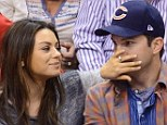 Under the thumb! Mila Kunis playfully silences fiancé Ashton Kutcher with her hand during basketball game... before 'making out' for the Kiss Cam
