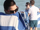 Not ready for her closeup! Anne Hathaway enlists five burly men to shield her with towels as she leaves the beach
