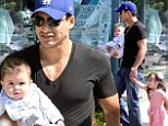 Family man: Mario Lopez carried baby son Dominic on Sunday during a family outing in West Hollywood, California