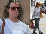 Make-up free Kim Basinger, 60, holds a floppy hat above her head to shield herself from the sun during trip to Whole Foods