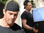 Josh Duhamel puts his gym toned muscles to good use to move furniture out of Brentwood home
