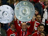 Nearly there: Bayern Munich supporters pose with mock-up Bundesliga titles ahead of the match in Berlin