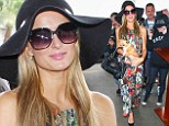 Not Leaving Without You: Paris Hilton does airport chic in floor-length floral frock... cradling her pampered pooch