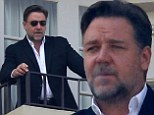 Even gladiators need a break! Russell Crowe takes in LA with while puffing a cigarette on hotel balcony