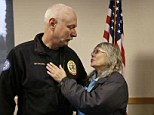 Reunion: Robin Youngblood, (right), smiles after embracing Snohomish County helicopter crew chief Randy Fay, who helped rescue her from the scene of a deadly mudslide days earlier, on Wednesday, March 26, 2014