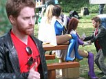He looks like he's having fun! Seth Green gets to grips with scantily clad superheros as he films anti-bullying advert
