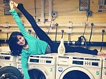 Just call her Hilarious Baldwin! New mom Hilaria makes even the most mundane of chores look fun as she pulls a yoga pose atop washing machine