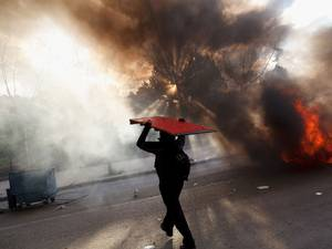 A protester carries a wooden table as he walks next to a burning barricade during a protest against the government's education reforms and cutbacks in university grants and staffing in Campus Ciudad Universitaria in Madrid
