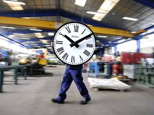 28 March 2014: An employee of the Bodet Company carries a clock at the plant of Trementines, France