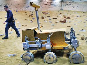 28 March 2014: Engineer Ben Nye walks past a robotic vehicle on the 'Mars Yard Test Area', a testing ground for the robotic vehicles of the European Space Agency's ExoMars program scheduled for 2018, in Stevenage