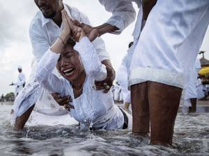 A Balinese woman cries while in a state of trance during Melasti Ceremony at a beach in Badung. The Melasti ritual is held annually ahead of the Nyepi Day of Silence, a ceremony intended to cleanse and purify the souls of the Balinese Hindu participants