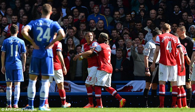 Stay away: Gibbs is restrained by Bacary Sagna as he protests the decision by Marriner