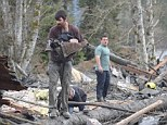 Hero and survivor: Kody Wesson pulls five-month-old baby Duke Saddarth from the debris left in the immediate aftermath of the Oso, Washington landslide which has claimed the lives of at least 18 people