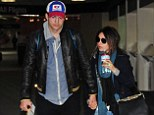 Ashton Kutcher takes 'pregnant' fiancee Mila Kunis home to see his family in Iowa... as she hides bump under baggy coat