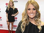 Glamming it up: Carrie Underwood looked stage ready as she hit the red carpet in Austin, Texas on Saturday at the iHeartRadio Country Festival n a quirky little black dress featuring a flowing panel of fabric on top