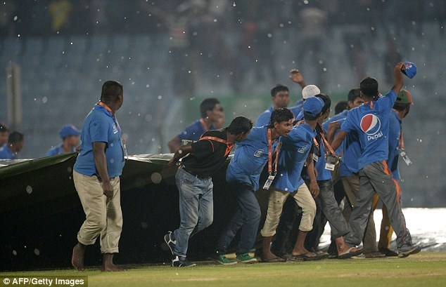 Over: The covers are brought on again in Chittagong as England's World Twenty opener ends in misery