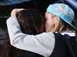Kiss me: Cara Delevingne and Michelle Rodriguez embrace before piling into a waiting car to go to a music festival in Miami