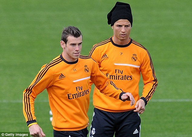 He's in fashion: Cristiano Ronaldo, wearing rather usual head gear, trains with Gareth Bale