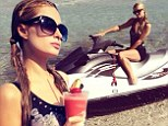 Paris Hilton keeps it modest in one piece swimsuit while enjoying a frozen cocktail in 'Paradise'