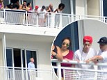 Justin Bieber and his nine-strong entourage gaze down from their Miami hotel balcony at annoyed gentleman below