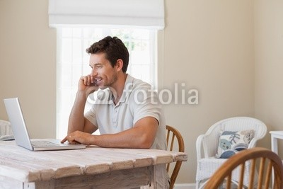 Young man using mobile phone and laptop
