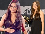 Mila Kunis poses with the Best Villain award in the press room during the 2014 MTV Movie Awards at Nokia Theatre L.A. Live