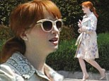 Christina Hendricks is pretty as a petal in blue-flowered dress and matching coat as she heads to a party