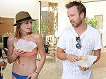 Pool party buddies: Ashley Greene showed off her svelte figure in a tiny orange and blue bikini while standing beside Breaking Bad star Aaron Paul in Palm Springs on Friday