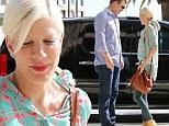 Finally a smile! Tori Spelling looks intrigued as she chats up handsome mystery man... while husband Dean McDermott is nowhere in sight