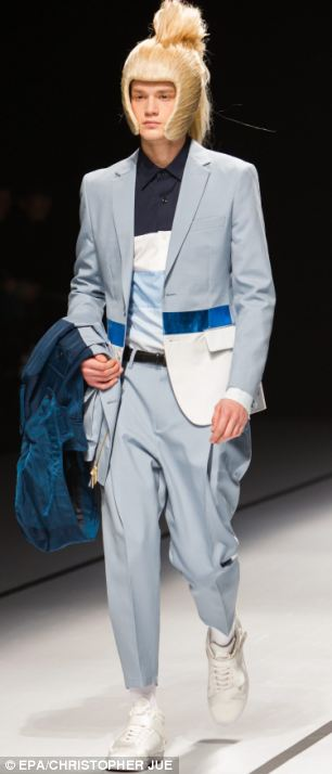 Two models don eye-catching blonde hairstyles and blue outfits as they take to the catwalk