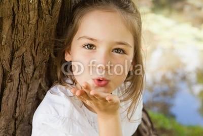 Close-up of a girl blowing a kiss at park