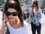 Let's chat! Katherine Schwarzenegger is thoroughly engrossed in phone conversation while dressed in sheer and loose-fitting white blouse