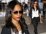 Zoe Saldana displays her slender legs in black skinny pants and leather riding boots at LAX