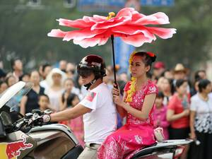 A woman arrives to take a part in a parade to celebrate the Dai ethnic group new year in Jinghong