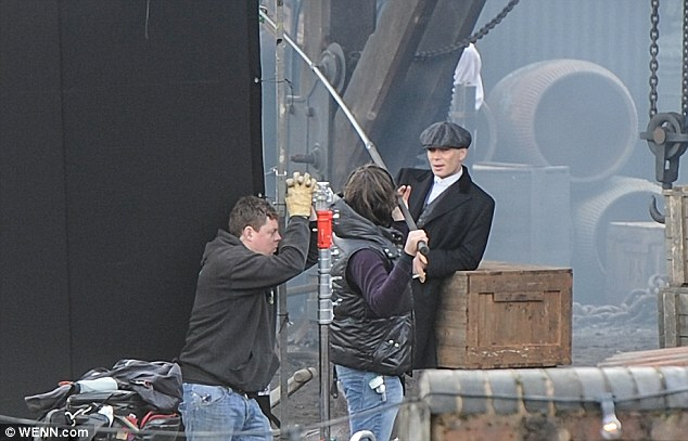 Don't mind me: The 37-year-old star leans against one of the many wooden trunks littering the set as the production team get into position