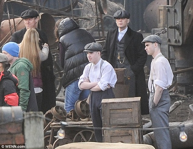 Passing the time: Cillian was joined by an array of young extras and production assistants