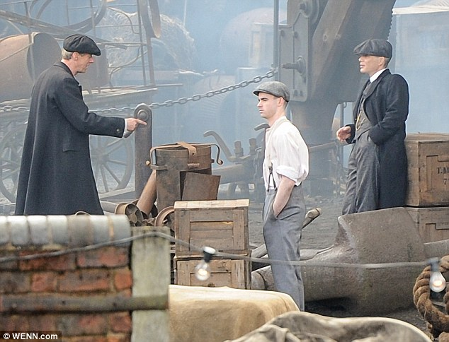 Pointing it out: The two actors chat as a young extra idles close by with his hands buried deep in his pockets