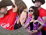 Baby's first country music festival! Ashton Kutcher protectively cradles Mila Kunis's blossoming belly as the couple heat up Stagecoach 2014