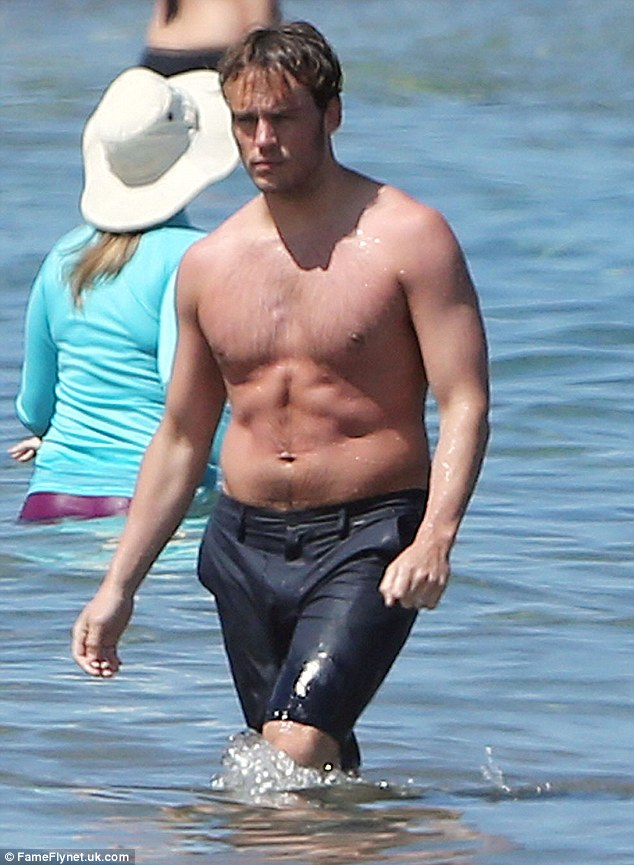 Check him out: The 27-year-old was looking pretty ripped as he walked through the water