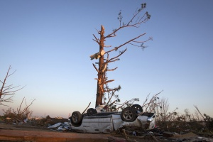 An upturned truck lies under a tree that has lost most of its branches, following a tornado near Vilonia, Arkansas, at sunset April 28, 2014. REUTERS/Carlo Allegri