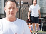 Tom Hanks cuts a lean figure in flips flops and shorts as he heads to wardrobe on set of A Hologram For The King in Berlin