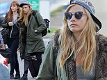 She's off: Cara Delevingne was seen arriving at Gatwick Airport wearing a fetching furry parka jacket on Tuesday before jetting out of London once again